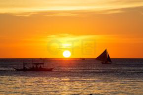 在日落时在热带海洋上的帆船。剪影照片.