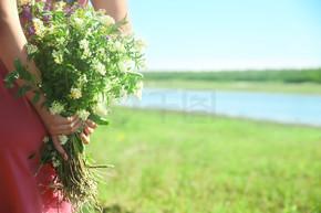 在户外捧着美丽花朵的年轻女子