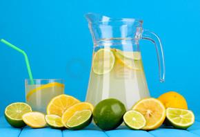 柑橘柠檬汁在投手和柑桔围绕在蓝色背景上的木桌上的玻璃