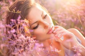 美丽的女孩躺在一片草地上,紫罗兰色的花朵