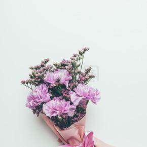 手持美丽典雅的紫色花朵与丝带隔离在灰色的人裁剪拍摄