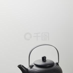 在红茶壶附近的木碗中选择性聚焦绿色火柴粉,在竹桌垫上加茶杯