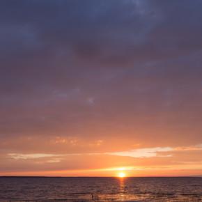 在美丽的落日下,一艘木制的渔船缓缓地在一个大湖面的浪花上摇曳,夕阳西下,水中映出美丽的天空和云彩