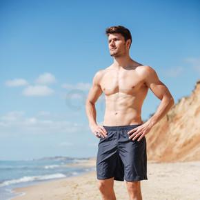 自信健壮的年轻男人站在海边
