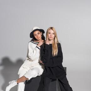 美丽的多元文化的朋友, 在黑色和白色的衣服坐在黑色的立方体上, 看着白色的相机