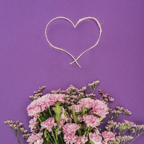 紫罗兰色的美丽的粉红色的花朵和心形的绳子花束