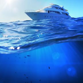 热带大海中美丽的阳光海景探险船,海底深蓝色,被水线隔开