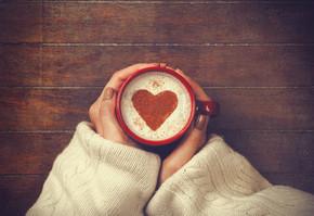 女子持杯热咖啡,与心的形状