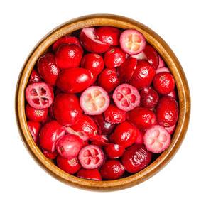 用木碗切碎和烘干的越橘.食用成熟的大头菜疫苗果实,带有酸味的红色浆果。衣服,从上面,白色背景,孤立的宏观食物照片.