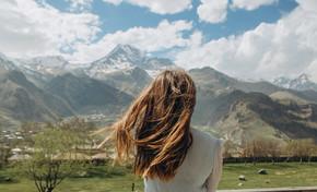 夏天后穿着连衣裙的女孩看着雪山的山峰