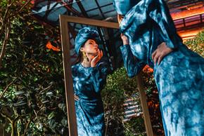 迷人的女人在蓝色礼服和头巾看着镜子在制革厂的低角度的看法