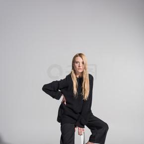 美丽的高加索金发碧眼的女人在黑色的衣服坐在椅子上, 看着相机在白色
