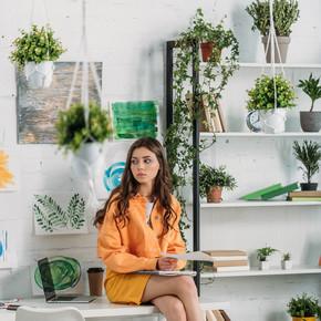 沉思的年轻女子坐在办公桌上,在房间里装饰着绿色植物和墙上的画