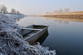冬天被遗弃的船停泊在河岸上.平静的河流,早晨,阳光和霜冻.