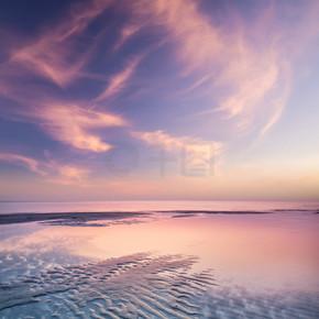 在日落期间在海边沙.