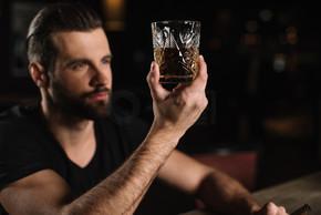 男子坐在酒吧柜台, 看着玻璃威士忌在酒吧