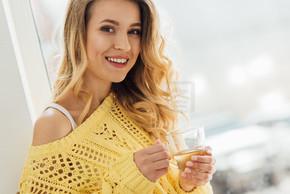 选择焦点美丽的微笑的年轻女子拿着一杯茶, 看着相机
