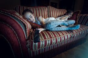 两个女孩睡在沙发上看电视的时候