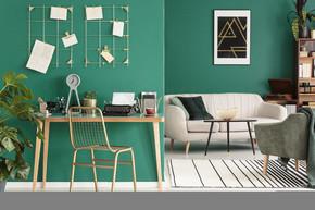 一个自由作家的家庭办公室用打字机由绿色墙壁与金黄框架组织者在时髦客厅内部