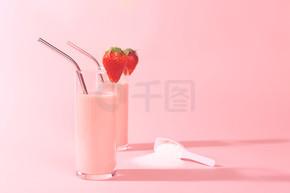 两个草莓冰沙和一个含有胶原蛋白粉末或蛋白质的罐子.
