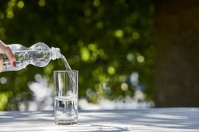 在阳光明媚的日子里,女人在木制桌子上用透明的杯子从瓶子里倒出新鲜的清洁水的剪影
