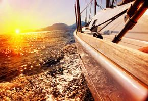 游艇帆船反对日落。帆船。乘快艇。帆船