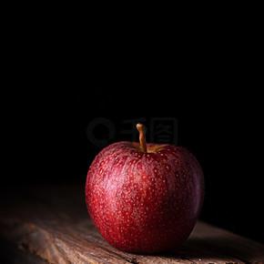 一个黑色背景的红苹果,垂直的