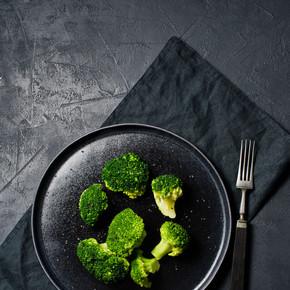 西兰花在一个黑色的盘子里。黑色背景, 顶部视图