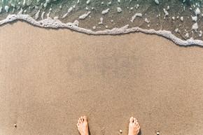 在沙子的蓝色波浪与男性脚