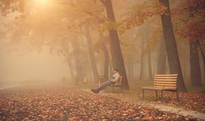 男人坐在一个大雾天公园的长凳上
