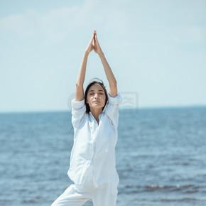 站立在体式 vrikshasana (树姿态) 的年轻妇女在海滩由海