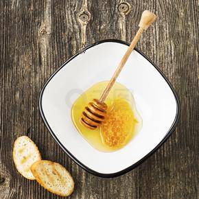 由新鲜花香或石灰蜂蜜中用于简单的灰色木背景蜂蜜的主轴漆包线简单村碗蜂窝蜜蜂蜡。顶视图.