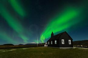 北极光在黑教会 Budir, 冰岛。极光在一个惊人的夜景。旅游目的地与美丽的绿色灯光景观.