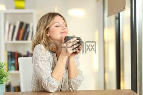 在家里拿着一个咖啡杯的妇女呼吸
