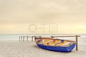 老黄蓝色木质小船在白色的沙滩上温暖日落大道上